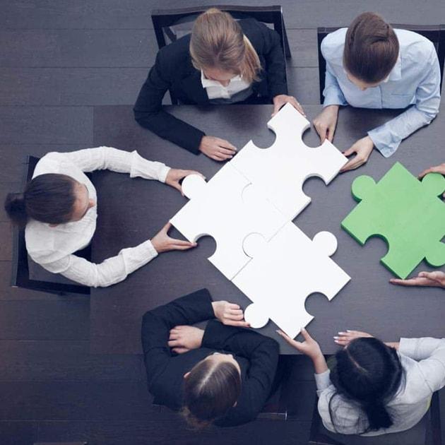Pesone sedute con grossi blocchi di puzzle in mano - realizzazione siti web
